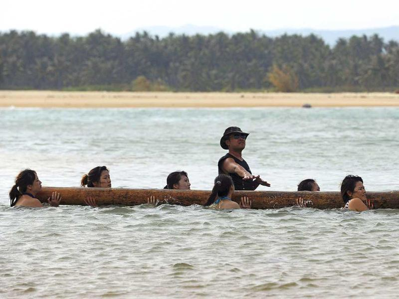 Trainees dressed in swimming suits carry a log on their shoulders as they walk through the sea. during a training session in Sanya, China. According to the security company, a total of 20 women, mostly college graduates, participated in the training session, which was the first open group training for female bodyguards in China. (Reuters)