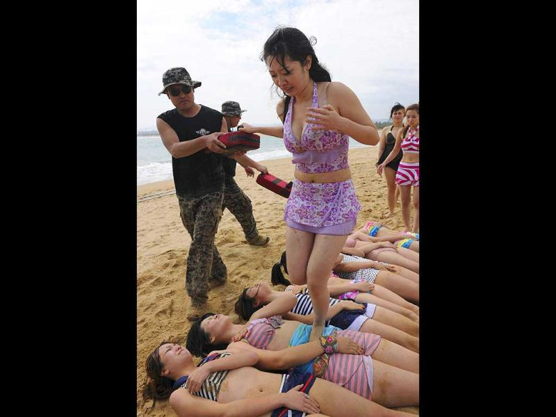 A trainee dressed in a swimming suit steps on the stomachs of other trainees with the help of a trainer from Tianjiao Special Guard/Security Consultant Ltd. Co. during a training session in Sanya, China. The company will offer the best trainee a chance to attend further study at the International Security Academy in Israel. (Reuters)