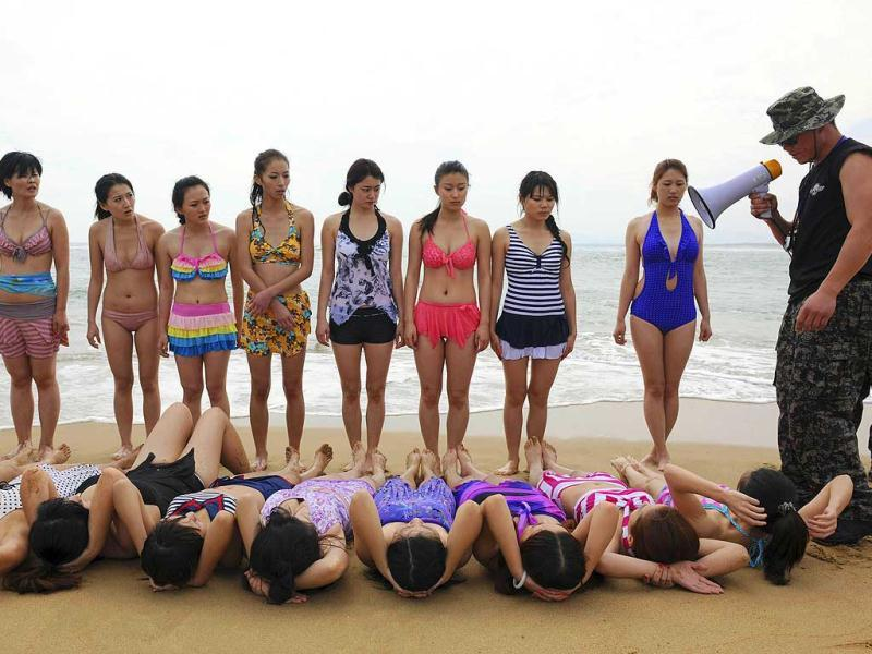 Trainees dressed in swimming suits follow the instructions of a trainer from Tianjiao Special Guard/Security Consultant Ltd. Co. during a training session in Sanya, China. (Reuters)