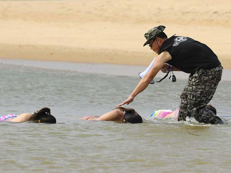 Trainees dressed in swimming suits sink their heads into the sea under the instructions of a trainer from Tianjiao Special Guard/Security Consultant Ltd. Co. during a training session in Sanya, China. All trainees will have to undergo 8-10 months of training to develop sufficient skills to serve their clients.(Reuters)