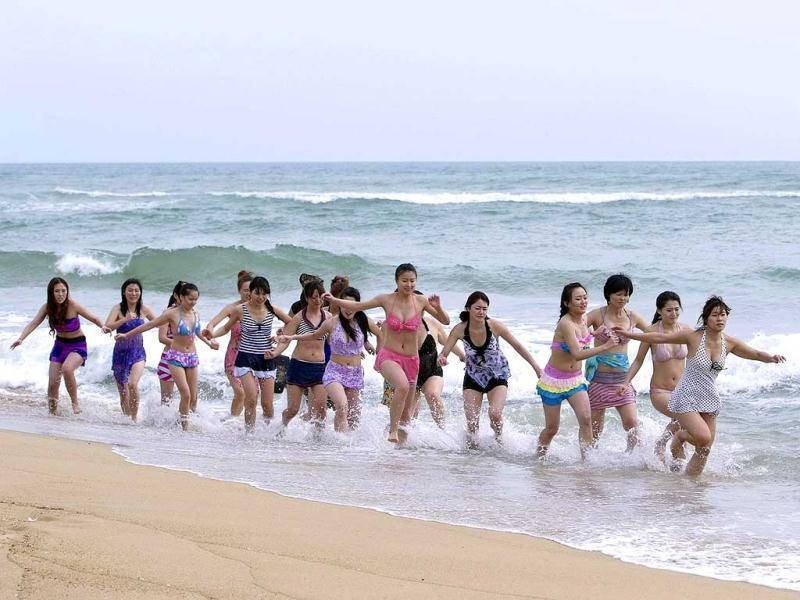Trainees dressed in swimsuits run through waves under the direction of a trainer from Tianjiao Special Guard/Security Consultant Ltd. Co. during a training session in Sanya, China. (Reuters)