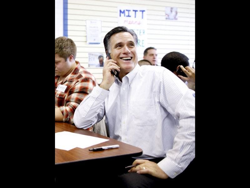 Republican presidential candidate, former Massachusetts Gov. Mitt Romney sits with volunteers and calls likely voters ahead of Tuesday's primary election during a visit to his campaign headquarters in Manchester. (AP Photo/Charles Dharapak)
