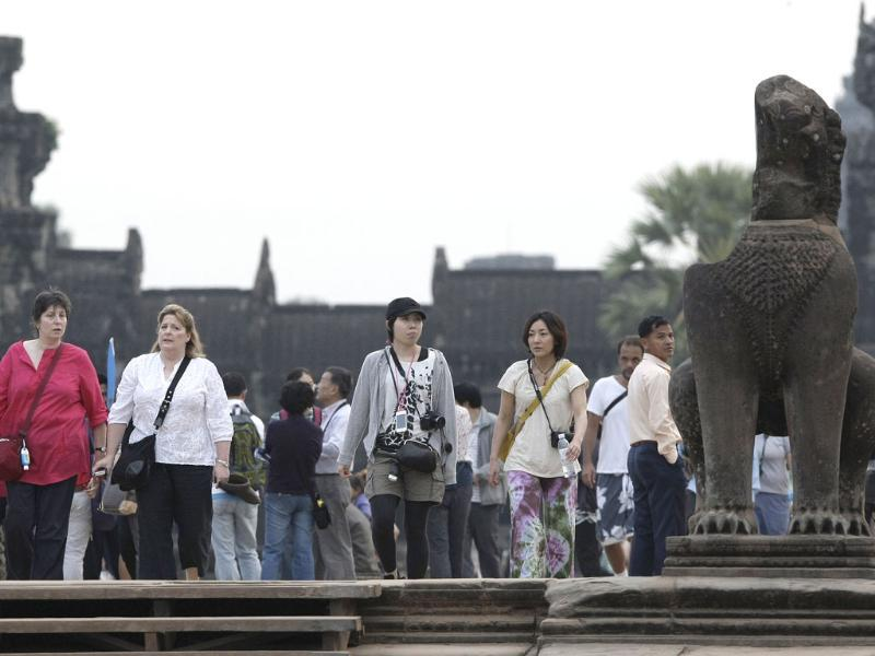 Tourists walk through the entrance to the famed Angkor Wat in Siem Reap province, some 230 kilometers northwest Phnom Penh, Cambodia. (AP Photo/Heng Sinith)