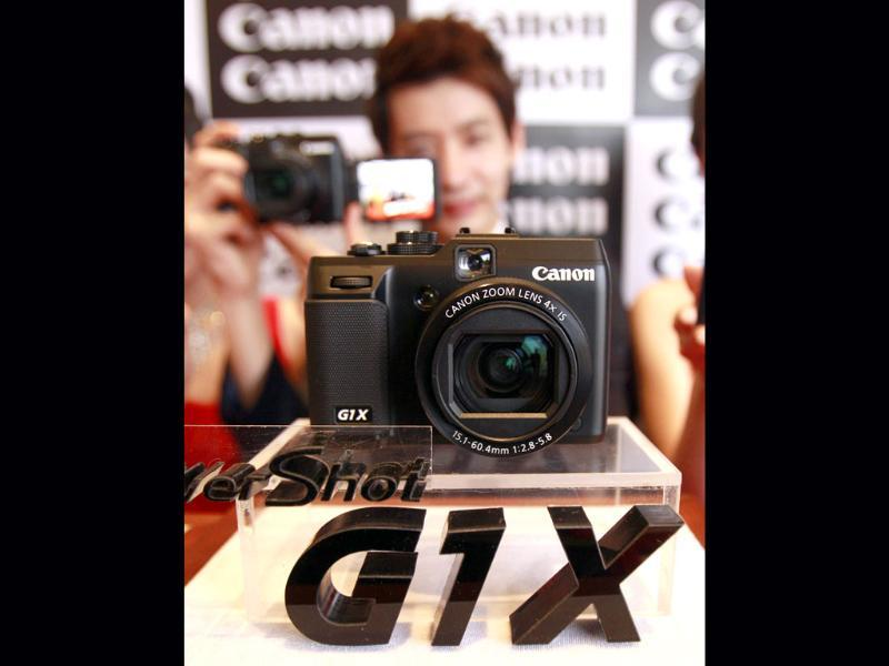 A model poses with Canon's new digital camera Power Shot G1 X during its unveiling ceremony in Seoul, South Korea. (AP Photo/Lee Jin-man)