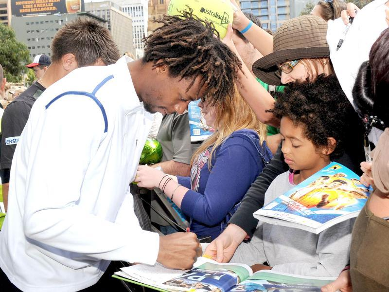 Tennis player Gael Monfils (L) signs autographs at a public event for the upcoming Kooyong Classic, in Melbourne. (AFP Photo/William West)