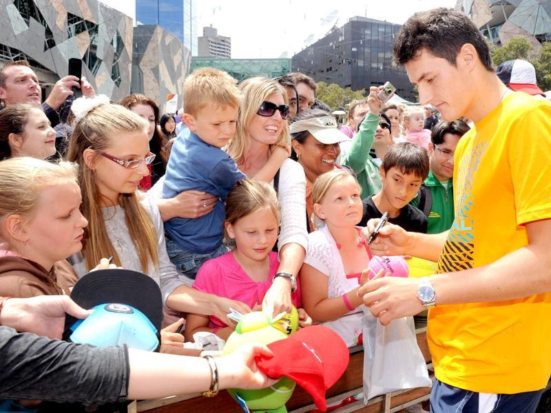 Tennis player Bernard Tomic of Australia (R) signs autographs at a public event for the upcoming Kooyong Classic, in Melbourne. (AFP Photo/William West)