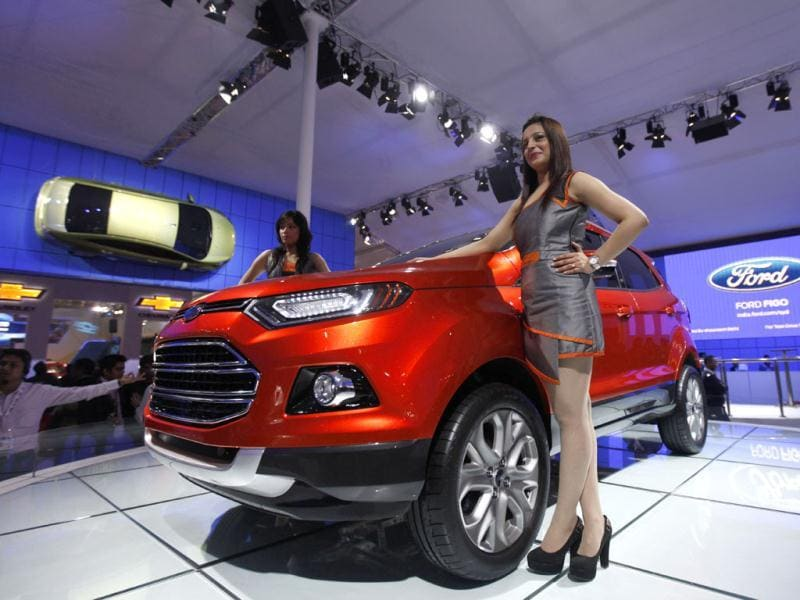 Models pose near a Ford Ecosport as a Ford Fiesta hangs suspended on a wall at the Auto Expo in New Delhi. AP Photo