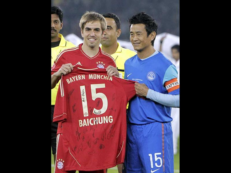 Baichung Bhutia, and Bayern Munich captain Philipp Lahm, exchange team jerseys at the start of their friendly match in New Delhi. (AP Photo/Gurinder Osan)