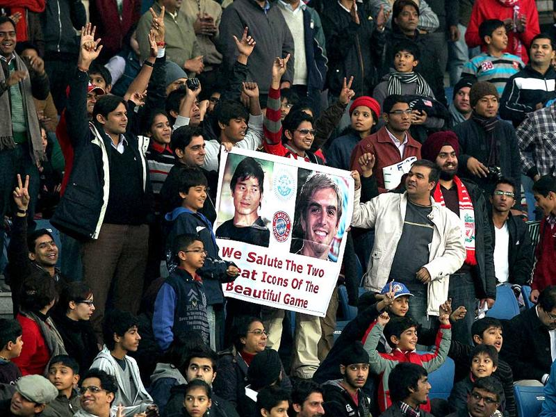 Indian football fans with a poster of Indian captain Bhaichung Bhutia and FC Bayern Munich team captain Phillip Lahm during an exhibition match at Nehru Stadium in New Delhi. (PTI/Vijay Verma)
