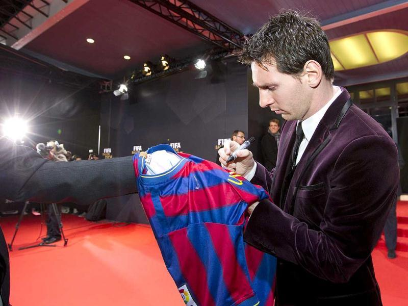 Soccer player Lionel Messi of Argentina signs a shirt ahead of the FIFA Ballon d'Or 2011 gala held at the Kongresshaus in Zurich, Switzerland. (AP Photo/Keystone, Alessandro Della Bella)