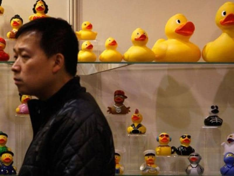 A man walks past toy ducks on display at the Hong Kong toys and games fair. AFP Photo
