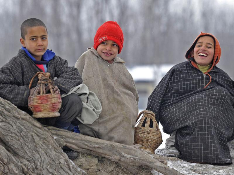 Children sit on a tree trunk holding traditonal heating pot called Kangri to warm themselves in Srinagar. AFP Photo/Tauseef Mustafa