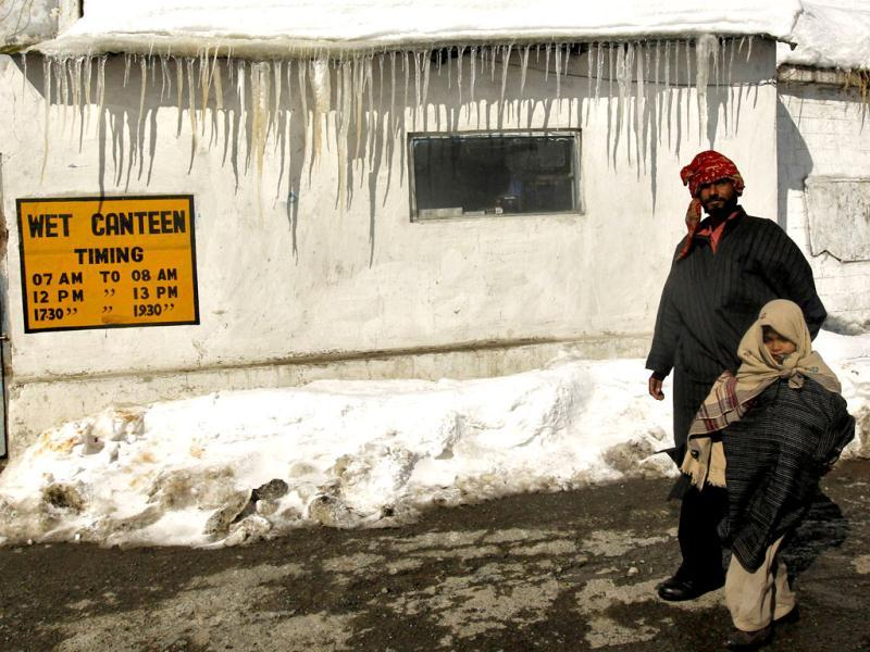 A man, along with his daughter, walks past a closed canteen belonging to security forces covered in snow and icicles on Srinagar-Jammu highway in Jawahar Tunnel area, 90 km (55 miles) south of Srinagar. Reuters Photo/Fayaz Kabli