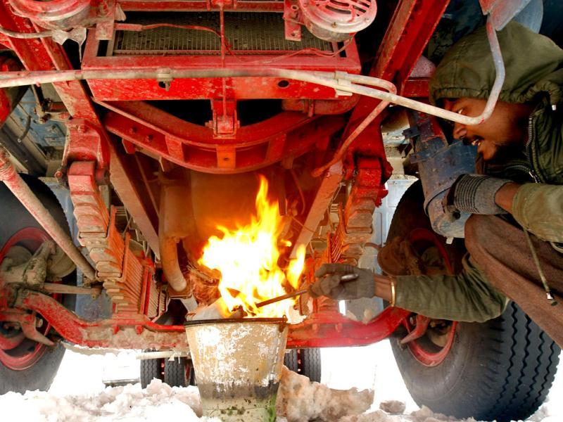 A stranded conductor burns a fire under his truck to keep the parts of truck warm while waiting for Srinagar-Jammu highway to reopen, in Qazigund, 70 km (43 miles) south of Srinagar. Reuters Photo/Fayaz Kabli