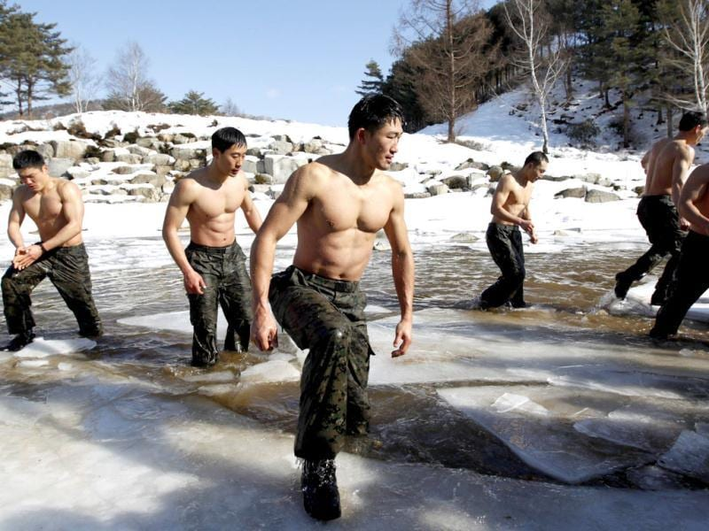Members of the Special Warfare Command get out of frozen waters after taking a cold bath during an annual severe winter season drill during a photo opportunity for the media in Pyeongchang. Reuters