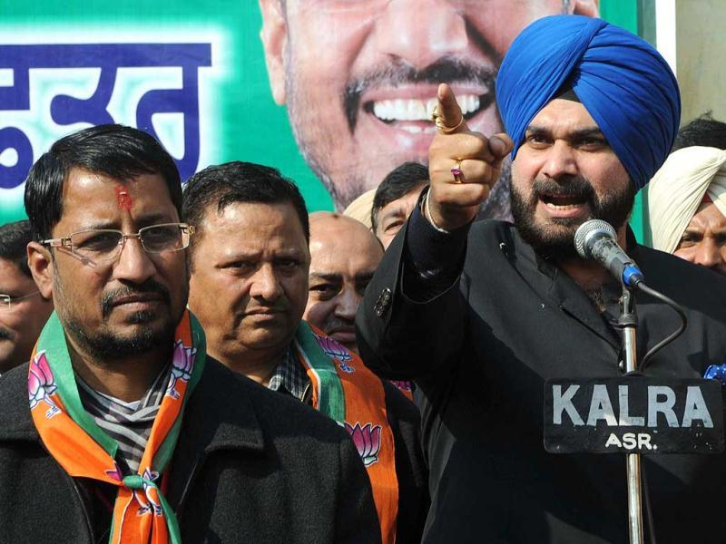 Former Indian cricketer and Bharatiya Janata Party (BJP) member of parliament Navjot Singh Sidhu (R), speaks to supporters next to Bhartiya Janata Party (BJP) candidate for the Member of Legislative Assembly (MLA) Anil Joshi (L) before to file his nomination papers to Additional Deputy Commissioner Development office in Amritsar on January 11, 2012. The state assembly elections are scheduled in five states and will be held on January 30, 2012. AFP Photo/Narinder Nanu