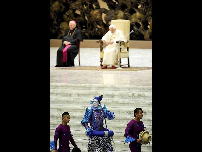 Circus artists walk past Pope Benedict XVI during his weekly general audience at Paul VI hall at the Vatican. AFP Photo/Filippo Monteforte.