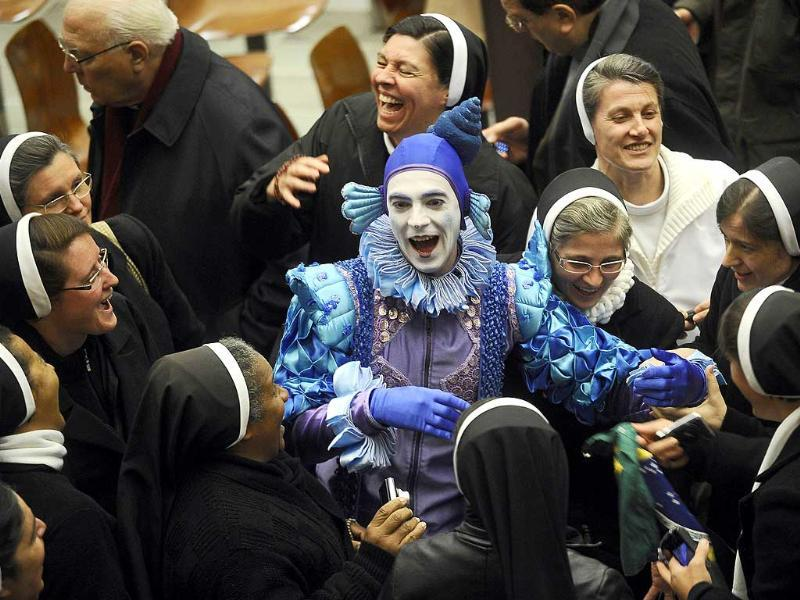 A clown jokes as he is surrounded by nuns at the end of Pope Benedict XVI's weekly general audience at Paul VI hall at the Vatican. AFP Photo/Filippo Monteforte.