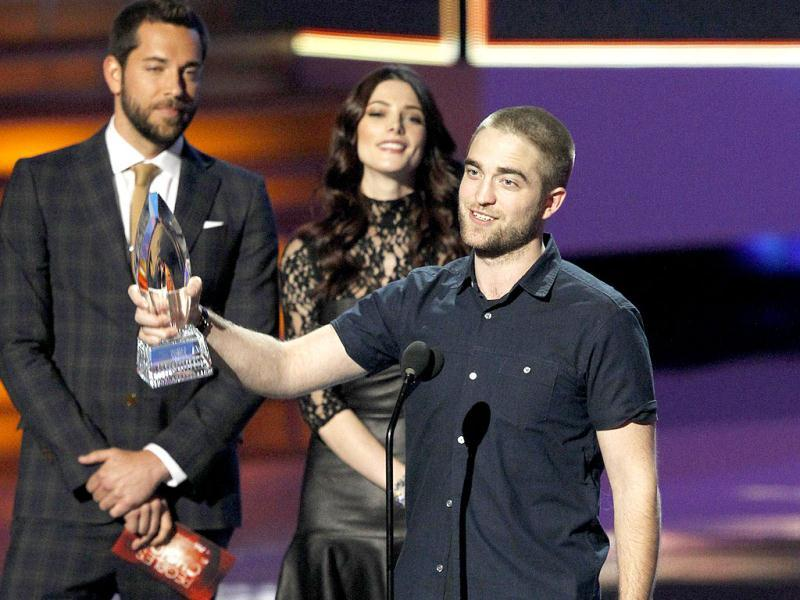 Robert Pattinson accepts the Favorite Drama Movie award for the film Water for Elephants from presenters Ashley Greene and Zachary Levi at the 2012 People's Choice Awards in Los Angeles. Reuters