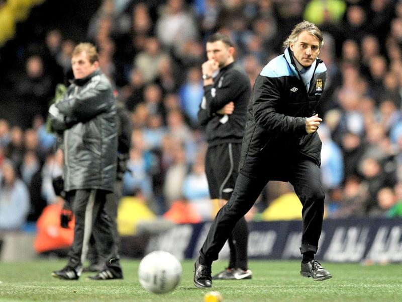 Manchester City's Italian manager Roberto Mancini runs after a loose ball, during the match against Liverpool during their English League Cup semi-final first leg soccer match at The Etihad Stadium, in Manchester, England. AP