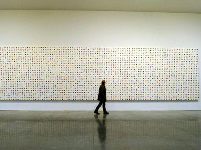A man walks past a painting titled Urea-13C during a media preview of The Complete Spot Paintings 1986–2011 by artist Damien Hirstat at the Gagosian Gallery in New York. AFP/Timothy A Clary