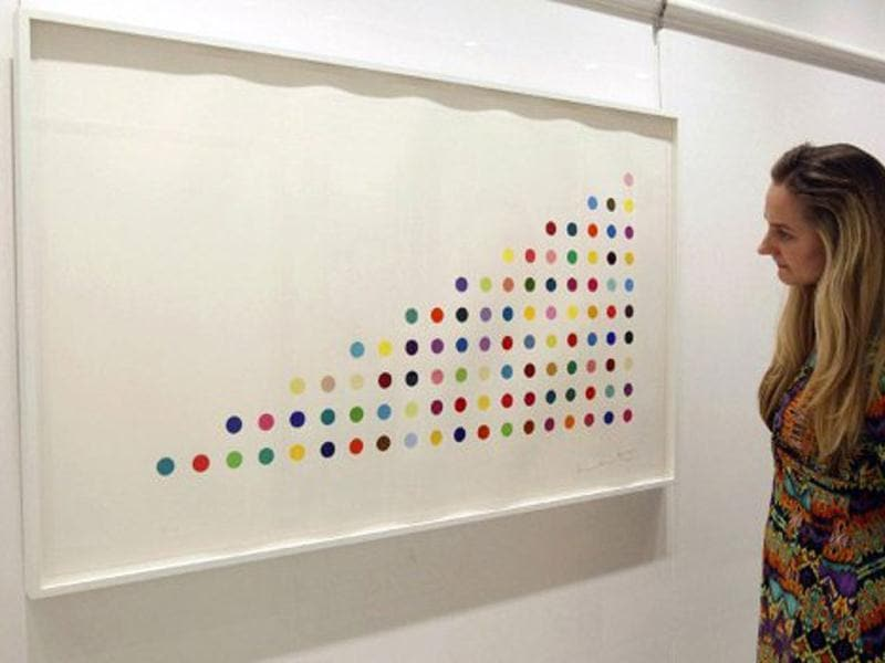 A member of staff from the Other Criteria art gallery poses for a photograph standing in front of new Spot Prints art work by British artist Damien Hirst in London. AFP/Justin Tallis