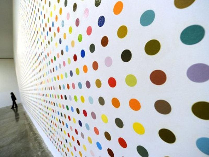 A woman walks past a painting titled Urea-13C during a media preview of The Complete Spot Paintings 1986–2011 by artist Damien Hirstat at the Gagosian Gallery in New York. AFP/Timothy A Clary
