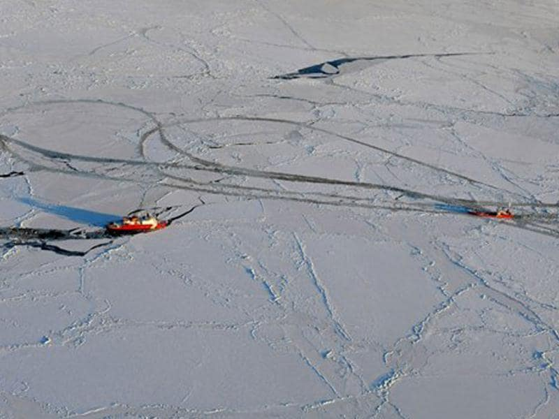In this photo provided by the US Coast Guard, the Coast Guard Cutter Healy, left, breaks through the Bering Sea ice 165 miles south of Nome, Alaska, on a return path to break ice up around the tanker Renda. AP photo
