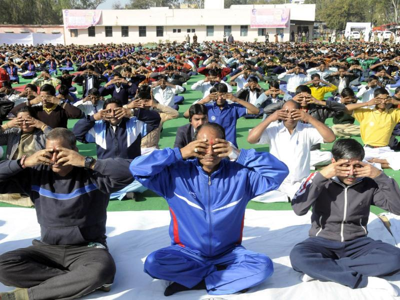 Madhya Pradesh chief minister Shivraj Singh Chouhan (C) joins school children in a mass surya namaskar yoga exercise in Bhopal. (AFP Photo)
