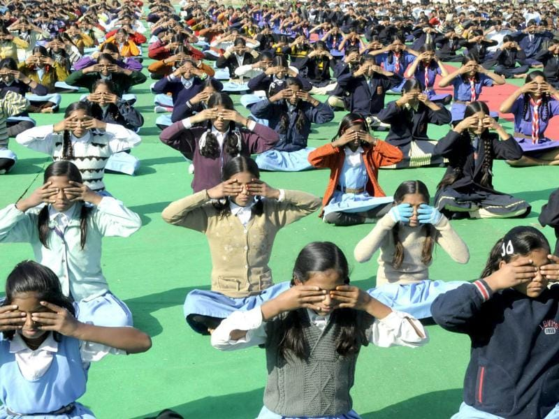 School children participate in a mass surya namaskar yoga exercise in Bhopal. (AFP Photo)