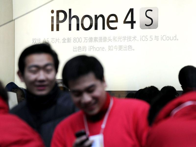 Apple employees wait for customers to buy the new iPhone 4S phones at an Apple store in Shanghai. AFP