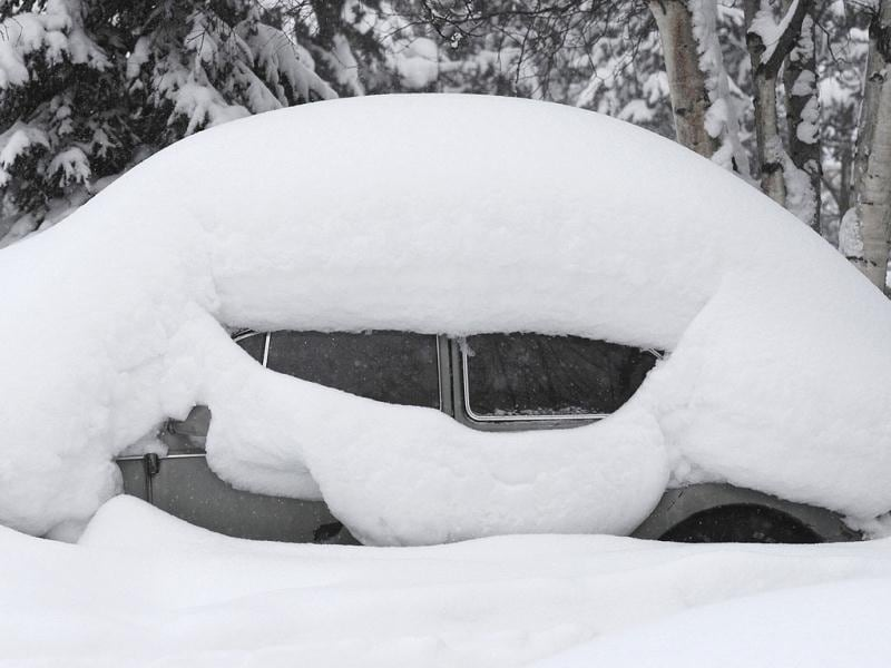 Snowfall outlines the familiar shape of a VW Beetle parked in Anchorage, Alaska. AP