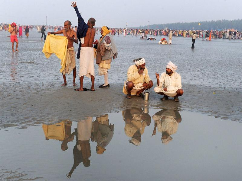 Pilgrims sit on the bank of holy river Ganga at the Gangasagar some 155km south of Kolkata. Thousands of pilgrims have started to converge for the Gangasagar Mela which will culminate in a dip in the ocean at the confluence of the River Ganges and the Bay of Bengal on the occasion of Makar Sankranti. AFP photo/Dibyangshu Sarkar