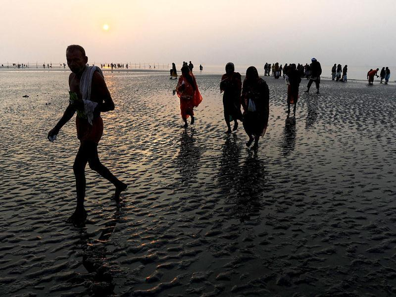 Pilgrims walk back after peforming rituals at the Gangasagar some 155km south of Kolkata. Thousands of pilgrims have started to converge for the Gangasagar Mela which will culminate in a dip in the ocean at the confluence of the River Ganges and the Bay of Bengal on the occasion of Makar Sankranti. AFP photo/Dibyangshu Sarkar