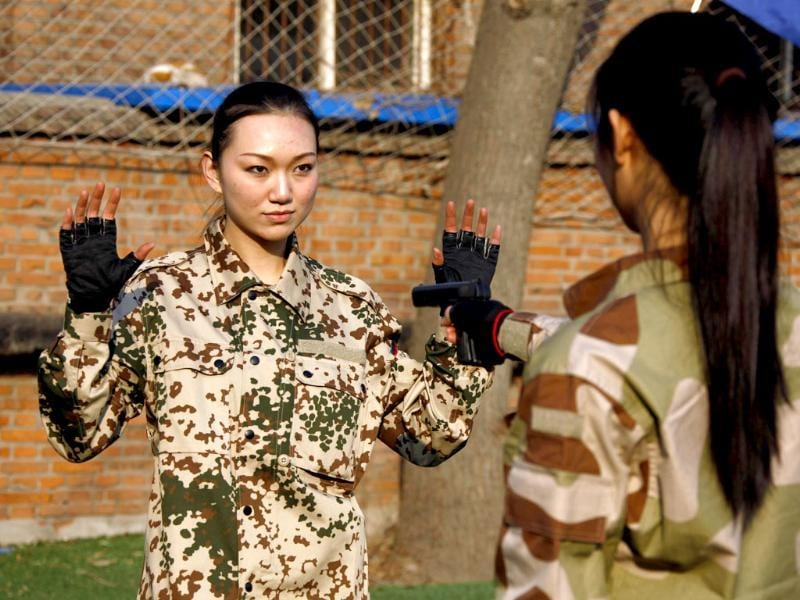 Female recruits use rubber guns to practice how to disarm an attacker during a training session for China's first female bodyguards in Beijing. (Reuters/David Gray)