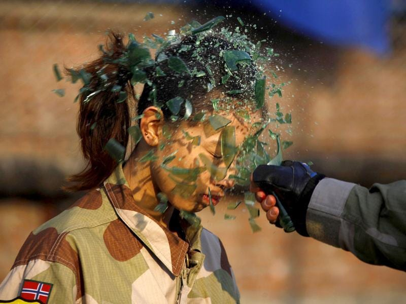An instructor from the Tianjiao Special Guard/Security Consultant Ltd. Co, smashes a bottle over a female recruit's head during a training session for China's first female bodyguards in Beijing. (Reuters/David Gray)