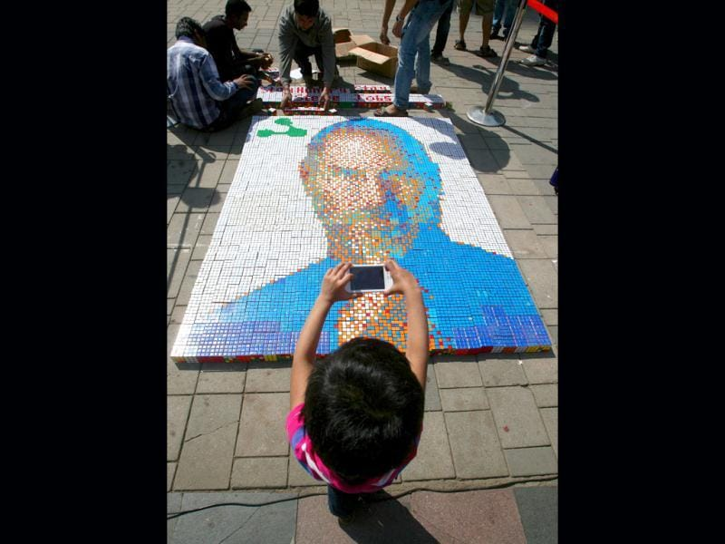 A young girl clicks a portrait of Apple co-founder Steve Jobs with her Apple iPhone as it is displayed at High Street Phoenix Courtyard in Mumbai. HT Photo/Kalpak Pathak