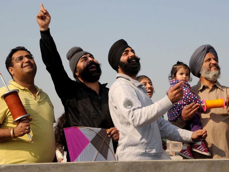 A Sikh family poses as they fly kites from during the Lohri festival in Amritsar. (AFP Photo/Narinder Nanu)