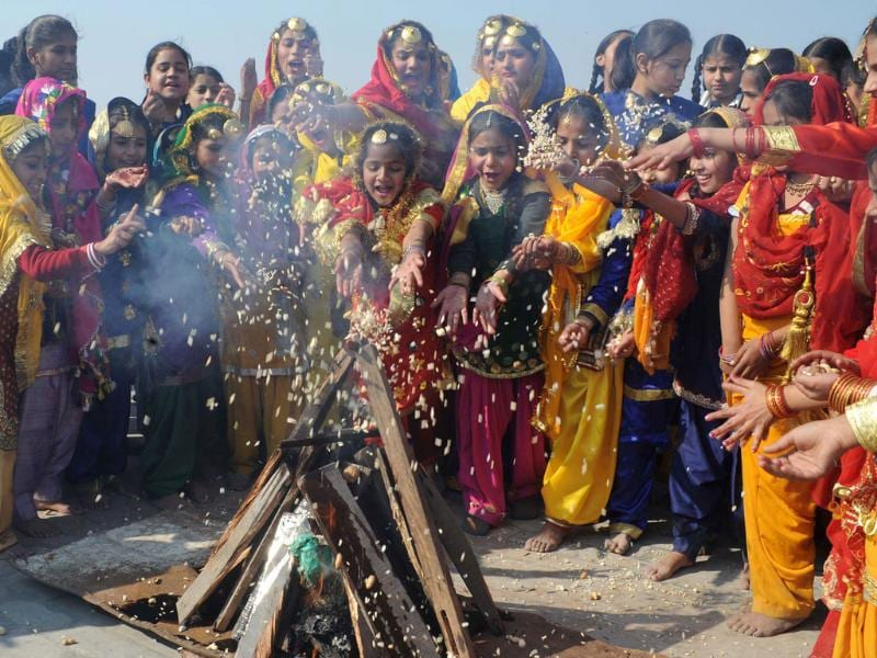 Girls dressed as Punjabi dancers gather around a bonfire at a school in Amritsar prior to the Lohri festival. (AFP Photo/Narinder Nanu)