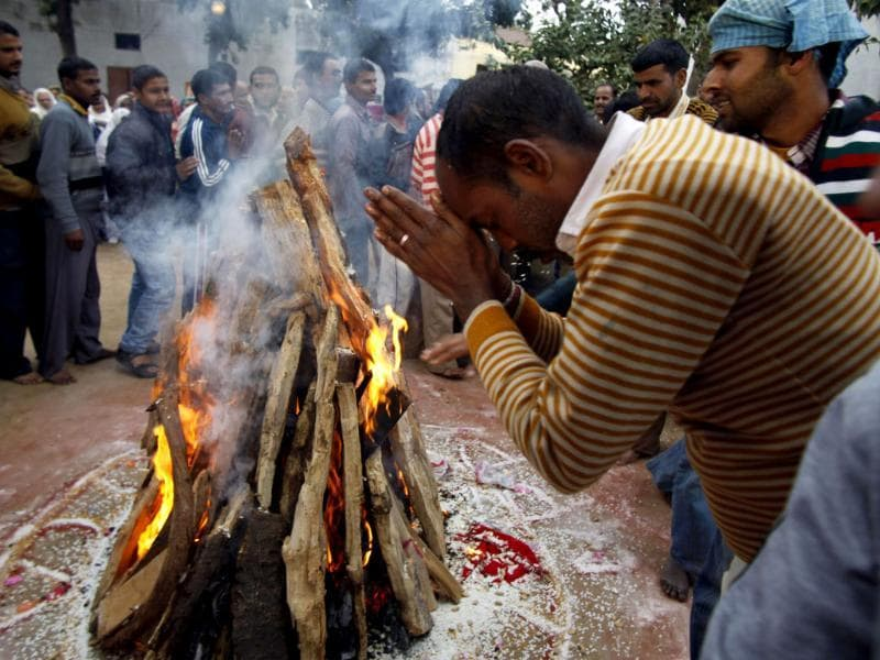 A prisoner prays in front of a bonfire as he joins in the Lohri festival celebrations at district Jail in Jammu. (AP Photo/Channi Anand)