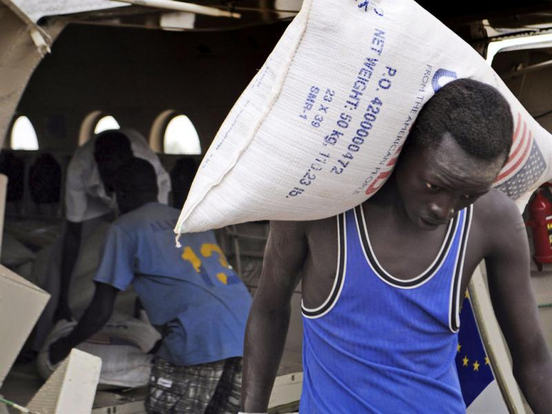Displaced residents of Pibor County, South Sudan, unload bags of food flown in by the World Food Program ar Pibor airport. (AP Photo)