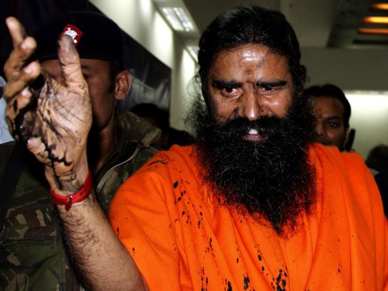 Swami Ramdev, with his face smeared with black ink, leaves the venue after addressing a news conference in New Delhi. An unidentified man threw black ink on Ramdev who was later caught by Ramdev's supporters, and then taken into custody and to the police station, local media reported. Reuters photo/B Mathur