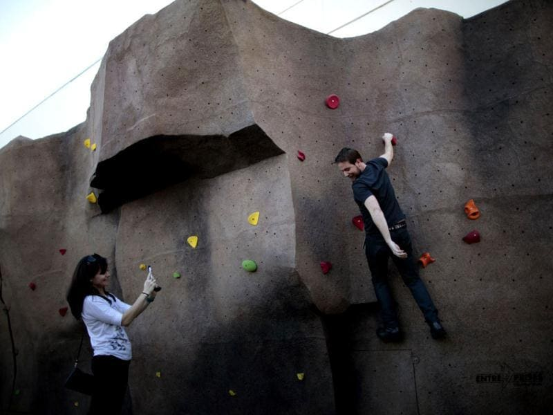 Systems Integrator Robert Scott, 32, (R) is photographed by his girlfriend Abby Pynes, 33, as he tries out the rock climbing wall at the Google campus near Venice Beach, in Los Angeles, California. Reuters