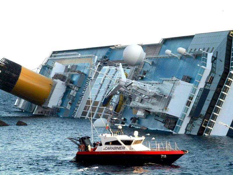 Three people died and several were missing after the cruise ship Costa Concordia ran aground and keeled over off an Italian island, sparking chaos as passengers scrambled to get off. (AFP Photo)