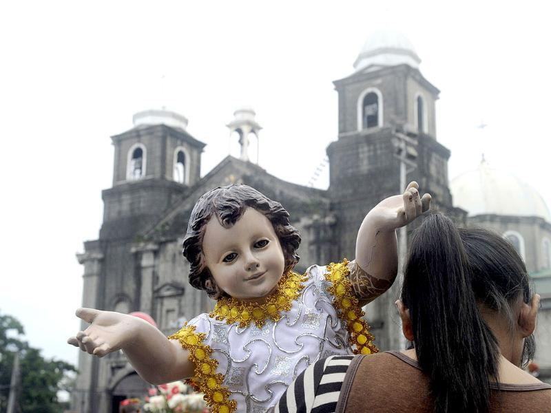 A resident of Manila's Tondo district holds a small religious icon of baby Jesus in the annual Sto Nino feast. AFP photo/Jay Directo