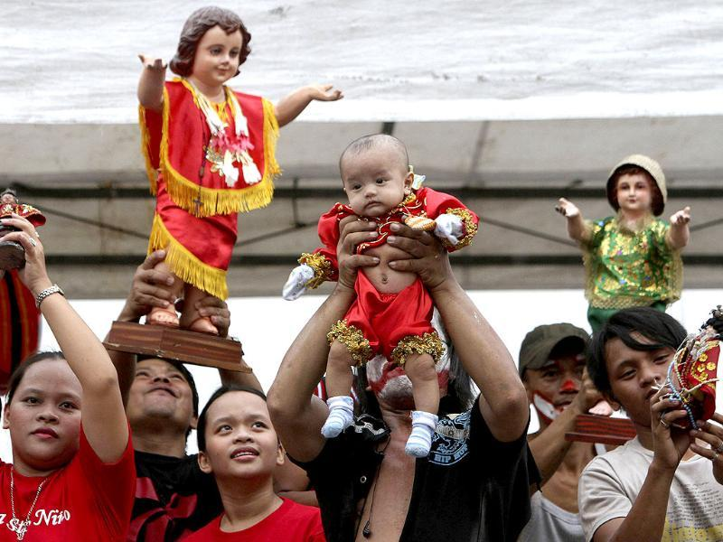 A devotee raises his son as others hold the statue of the infant Jesus, as they celebrate the feast of the Sto Nino in Moriones, Tondo, metro Manila. Reuters photo/Romeo Ranoco