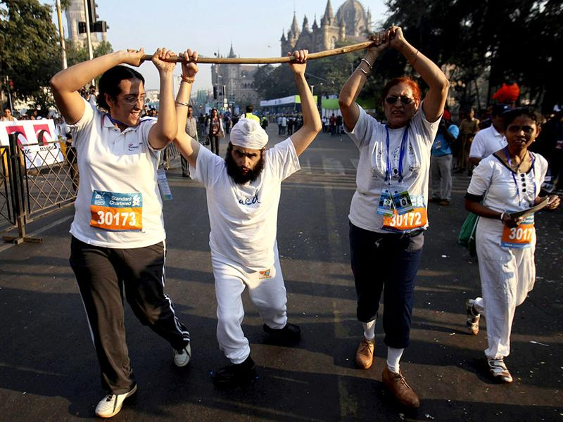 Physically impaired Angad Dev Singh (C) walks with the help of family members during the Mumbai Marathon. Reuters/Danish Siddiqui