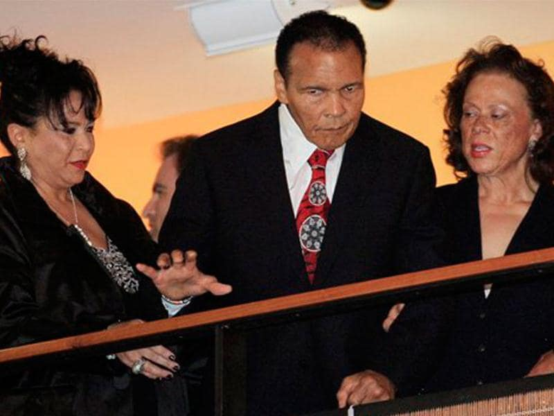 Boxing great Muhammad Ali is helped by his wife, Lonnie, right, and sister-in-law Marilyn Williams, left, as he looks down from a balcony at friends attending a celebration for his 70th birthday at the Muhammad Ali Center, in Louisville, Kentucky. Ali turns 70 on Tuesday. (AP Photo/Mark Humphrey)