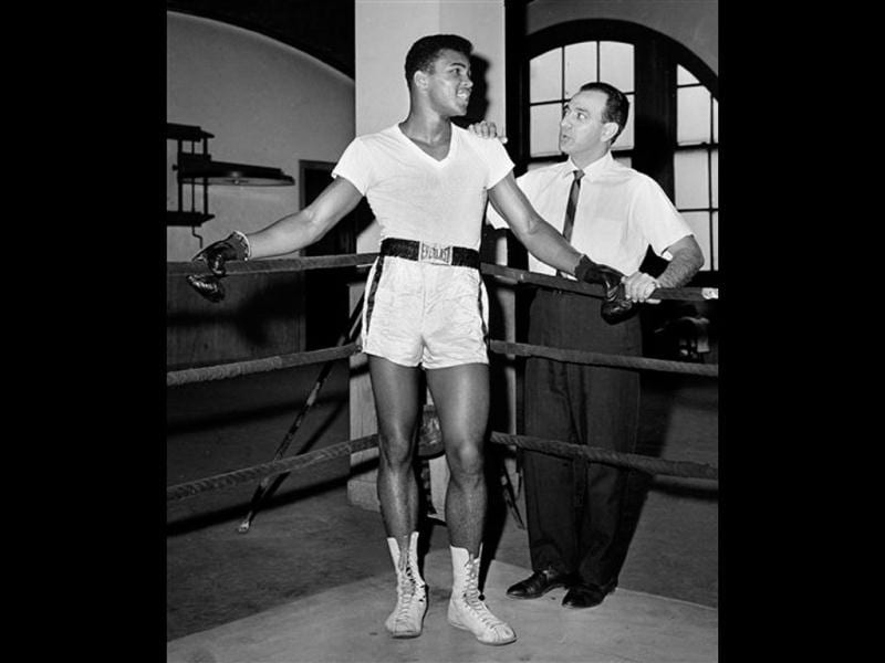 In this Feb 8, 1962, file photo, young heavyweight fighter Cassius Clay, who later changed his name to Muhammad Ali, is seen with his trainer Angelo Dundee at City Parks Gym in New York. Ali turns 70 on Jan. 17, 2012. (AP Photo/Dan Grossi, File)