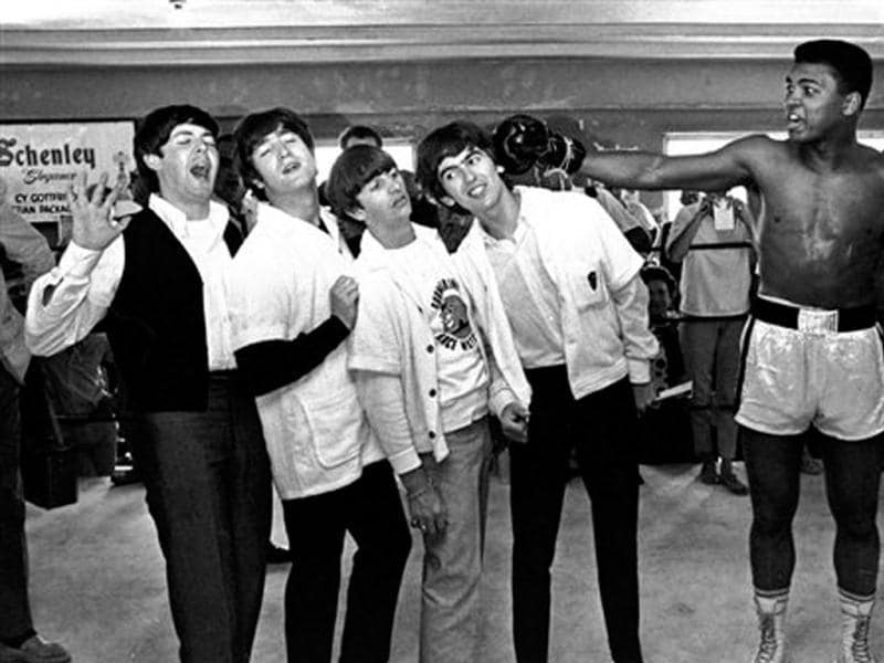 In this Feb 18, 1964, file photo, The Beatles, from left, Paul McCartney, John Lennon, Ringo Starr, and George Harrison, take a fake blow from Cassius Clay, who later changed his name to Muhammad Ali, while visiting the heavyweight contender at his training camp in Miami Beach, Florida. Ali turns 70 on Jan. 17, 2012. (AP Photo/File)